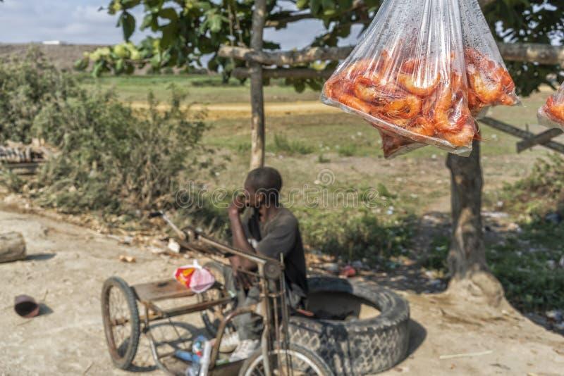 SUMBE/ANGOLA - 28 de outubro de 2017 - retrato do vendedor ambulante rural africano Vendendo camarões fotografia de stock