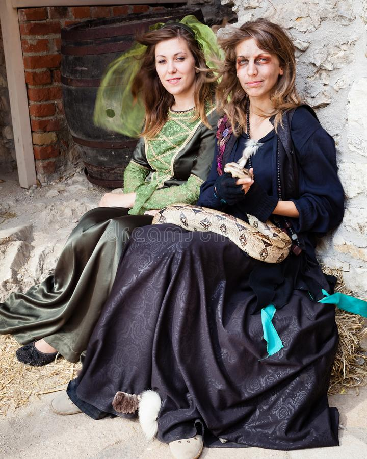Girls in Middle Eval Clothes and Snake at Castle stock photos