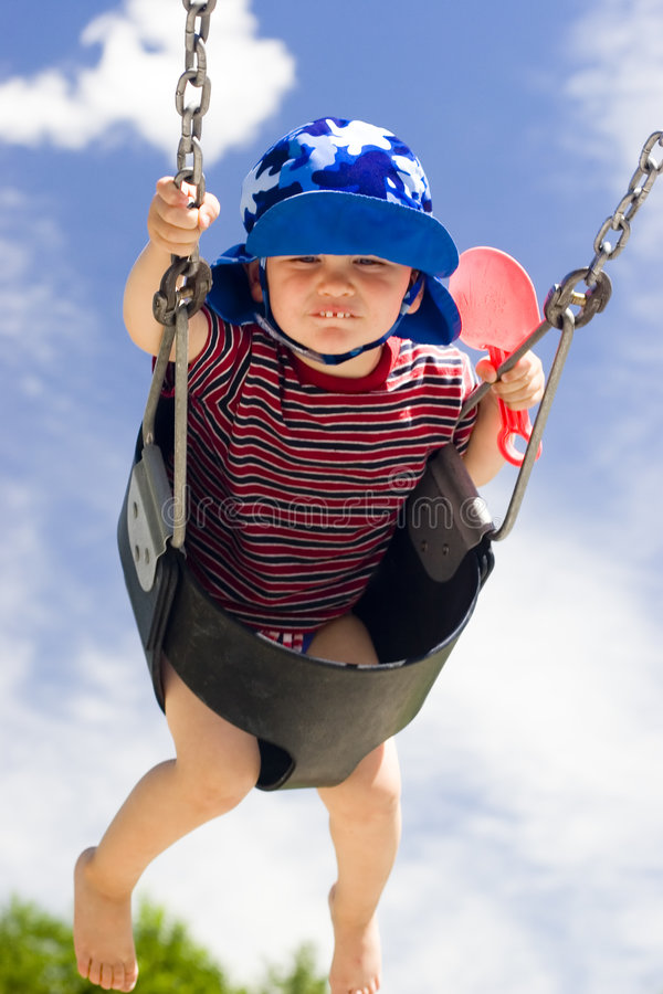 Summer. Boy swings against blue summer sky with clouds at park stock photos