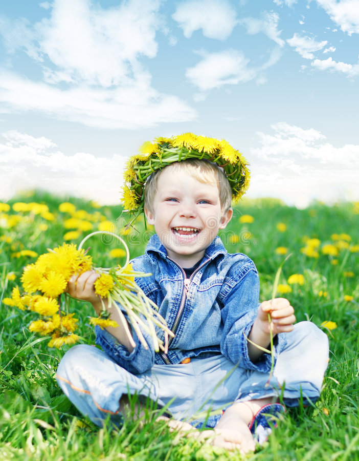 Summer. Happy kid laugh with diadem and dandelions on green grass royalty free stock photo