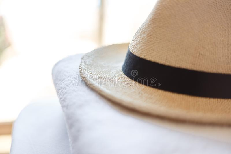 Summer accessories for the beach. Heart-shaped sunglasses, stylish knitted straw hat and white towels. Minimal summer concept. Flat lay. Copy space. Top view royalty free stock photography