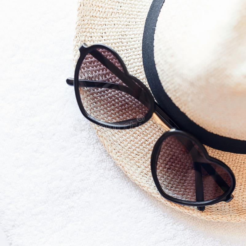Summer accessories for the beach. Heart-shaped sunglasses, stylish knitted straw hat and white towels. Minimal summer concept. Flat lay. Copy space. Top view stock image