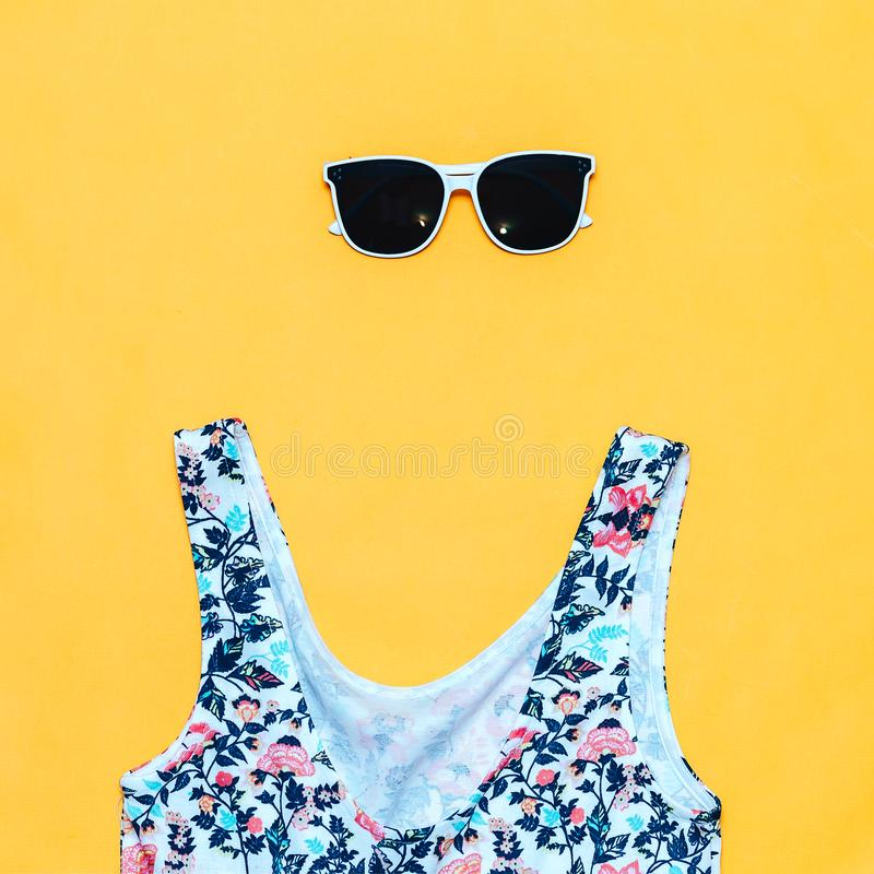Summer accessories concept on yellow background, flatlay, copyspace, vintage camera, white sunglasses and swimsuit stock photography