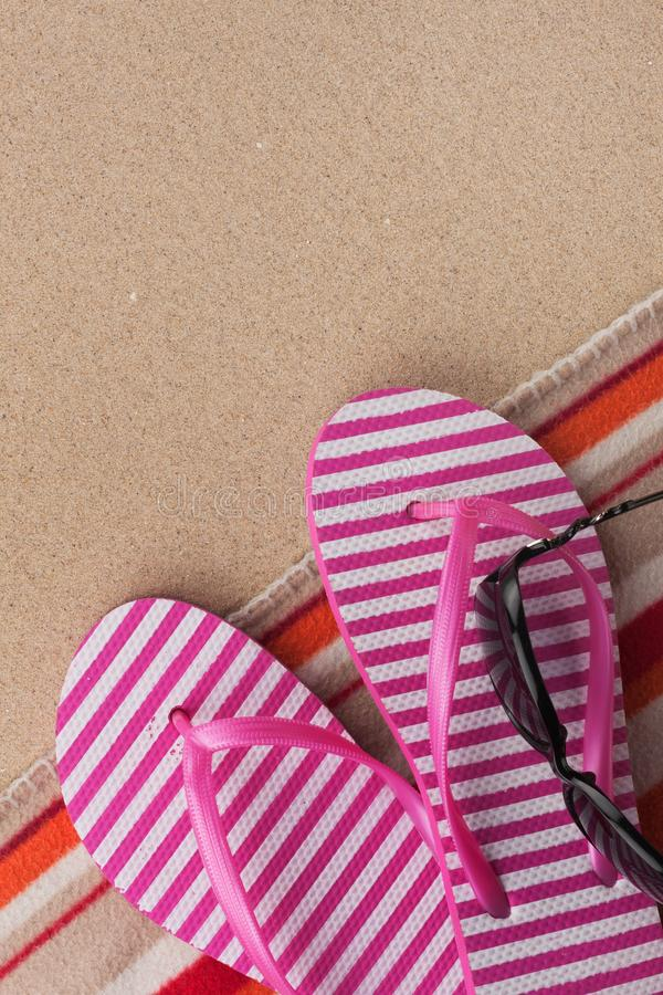 Summer accessories flip flops and towel. Sand beach texture background stock images