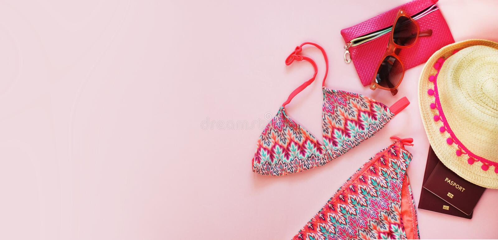 Summer Accessories, Straw hat with Pink ribbon, Swimsuit, Sunglasses, Passport, over Pink Background. Baner. stock images
