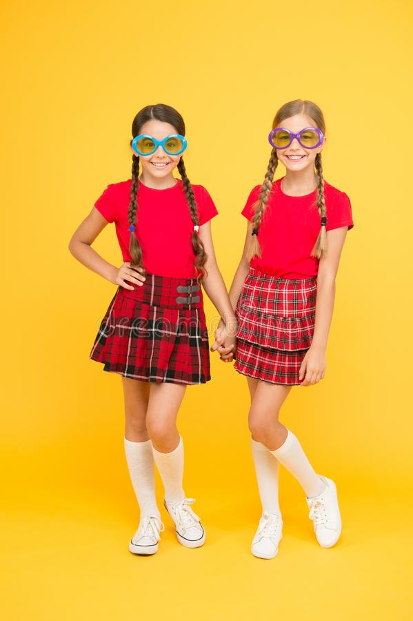 Summer accessory. Girls cute sisters similar outfits wear colorful sunglasses for summer season. Summer fashion trend stock photo