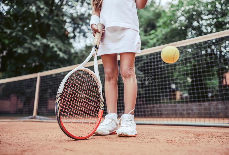 Summer activities for children in the tennis club. Cropped image of sports little girl on tennis court. Athletic child girl hits stock photos
