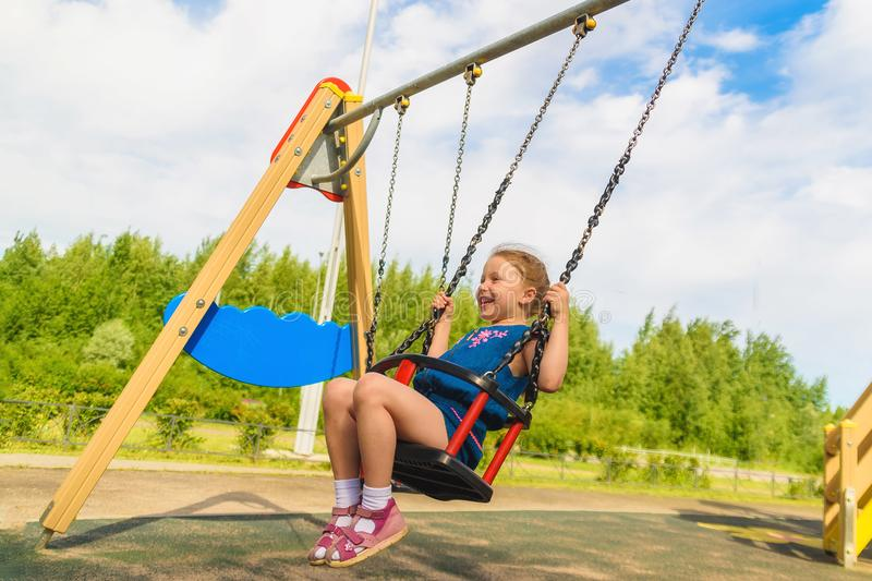 Summer activity. Small kid playing in summer. Happy laughing child girl on swing. childhood daydream .teen freedom. romantic royalty free stock image