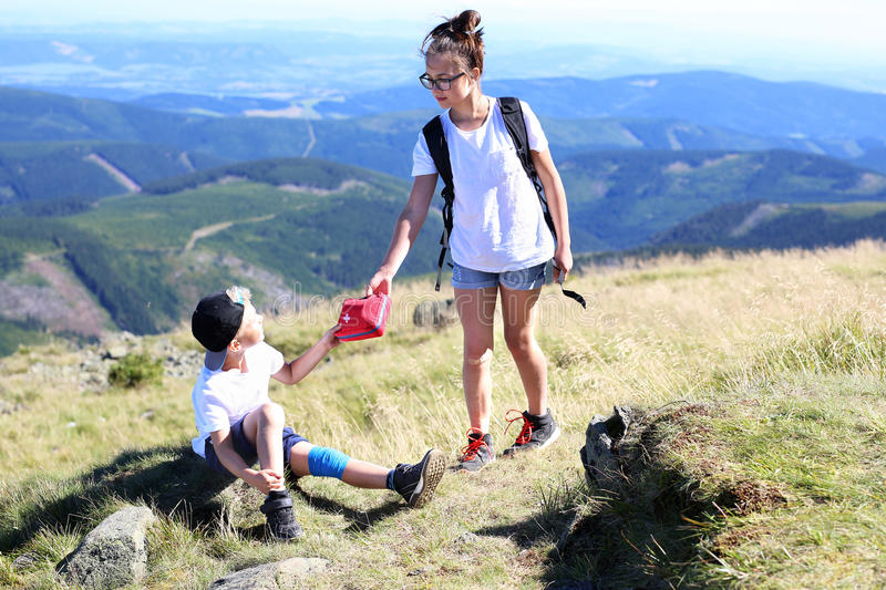 Summer adventure expedition in the mountains. Girl gives the boy to do a first aid kit stock photo