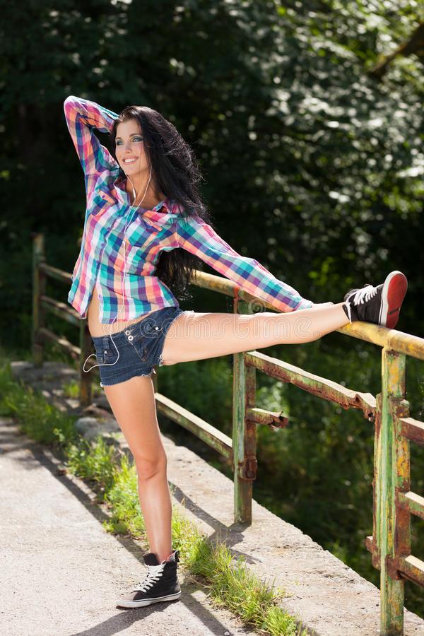 Summer aerobics. Smiling sporty girl stretching on the bridge royalty free stock photography