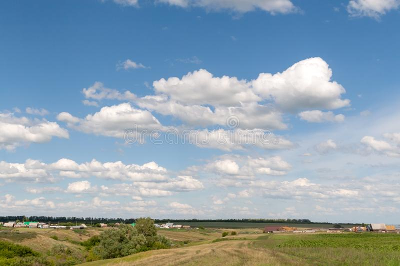 Summer afternoon over a Russian village. Beautiful white clouds in the blue sky over the Russian village stock photos