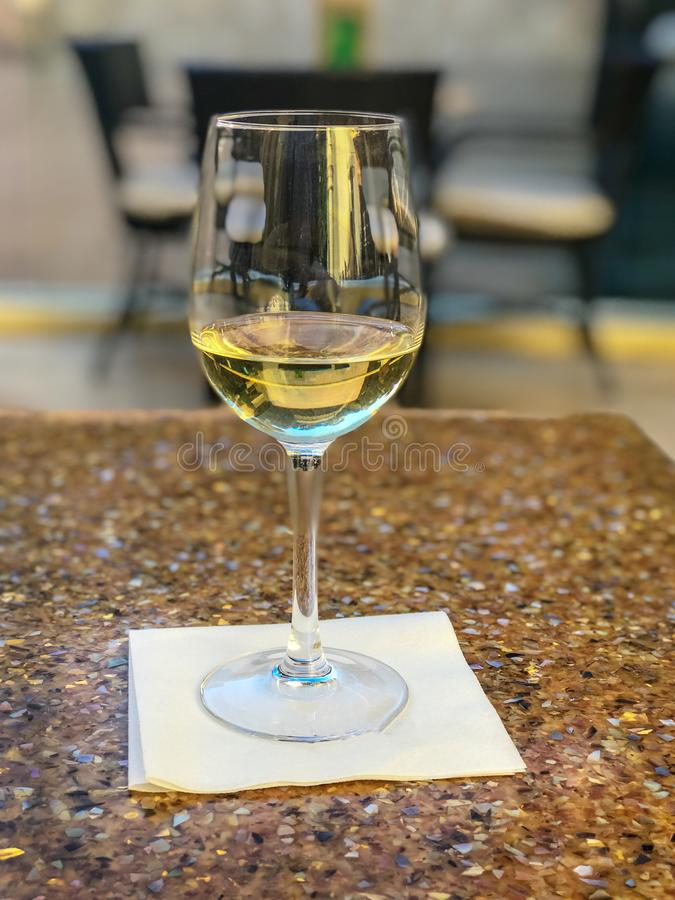 White Wine Fills Glass on Cafe Table. Summer afternoon at a sidewalk cafe to enjoy glass of white wine royalty free stock image