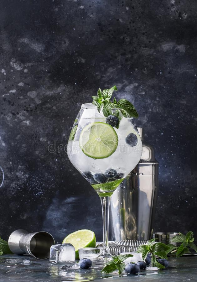 Summer alcoholic cocktail blueberry mojito with rum, green mint, lime and crushed ice, bar tools, gray bar counter, selective. Focus royalty free stock photos