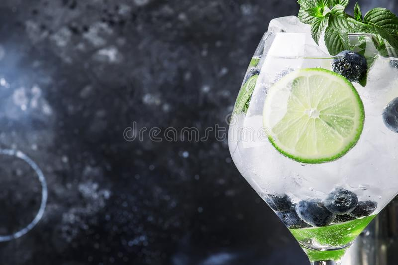 Summer alcoholic cocktail blueberry mojito with rum, mint, lime. And ice, bar tools, gray background, selective focus royalty free stock photos