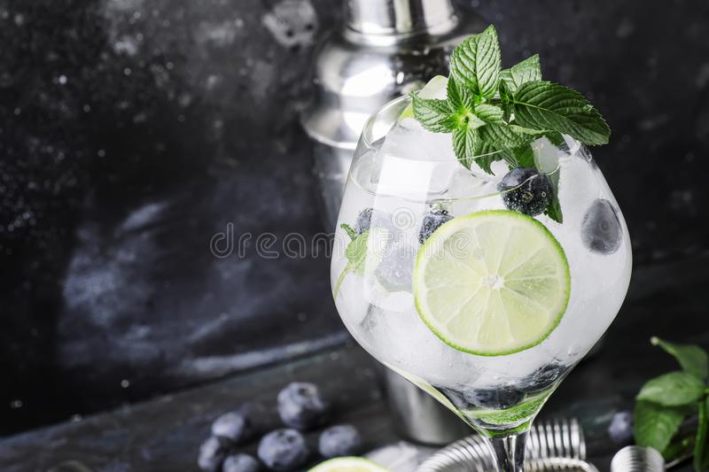 Summer alcoholic cocktail blueberry mojito with rum, mint, lime. And ice, bar tools, gray background, selective focus stock photos