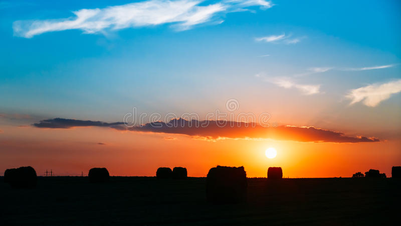 Summer Autumn Field Meadow With Hay Bales. Silhouettes Under Sunset Sunbeams. Bright Sky And Dark Ground Panorama. Sun Over Rural Countryside Field At Dawn Or royalty free stock image