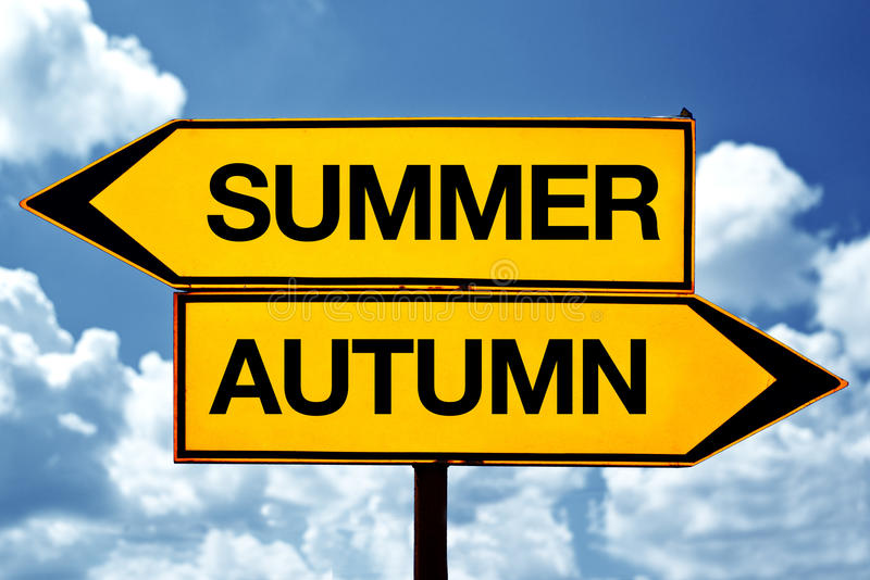Summer or autumn opposite signs. Two blank opposite signs against blue sky background royalty free stock photo