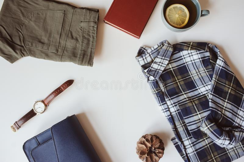 Summer or autumn woman casual fashion set flat lay with copy space. Plaid shirt, blue cross body bag and khaki pants on white background. Stylish outfit top stock photography