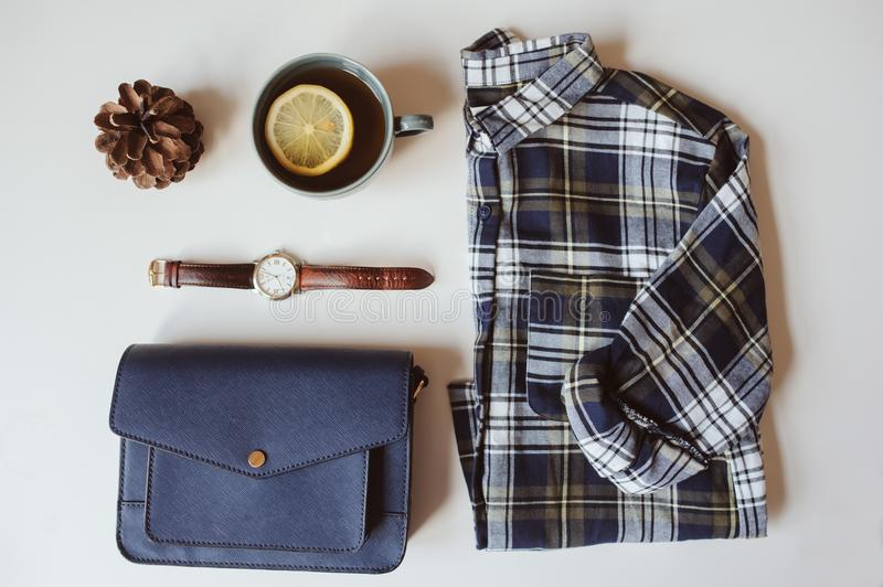 Summer or autumn woman casual fashion set flat lay. Plaid shirt, blue cross body bag and watch on white background. Stylish outfit top view royalty free stock images