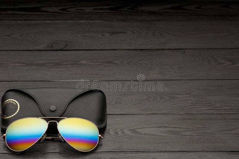 Summer aviator sunglasses with mirrored color lenses made of glass in a metal frame of gold color with a black leather case on a stock photo