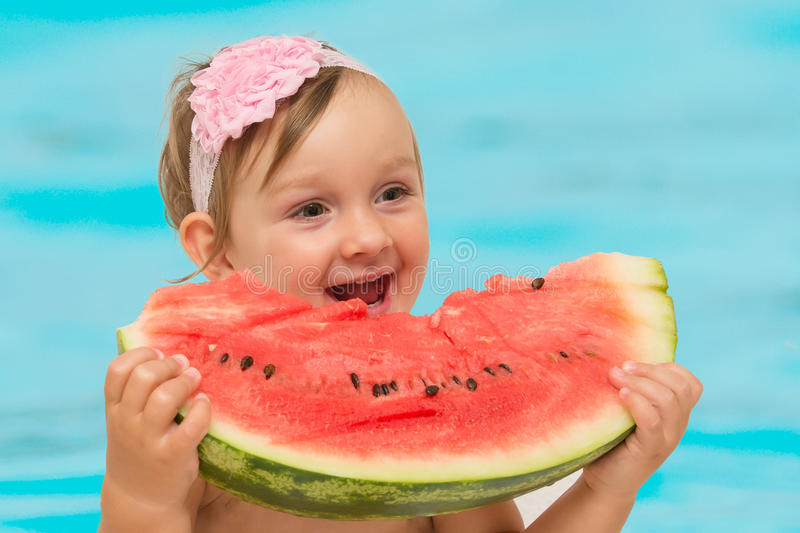 Summer baby girl eating watermelon stock photos