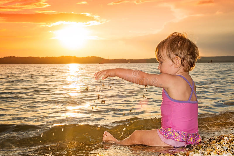 Summer baby girl playing in sea at sunset royalty free stock images