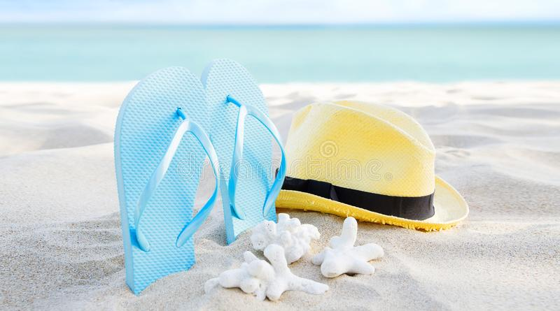 Summer background banner with flip flops. Vacation holiday accessories on beach. Slippers, hat and shell on sand near ocean. stock photography