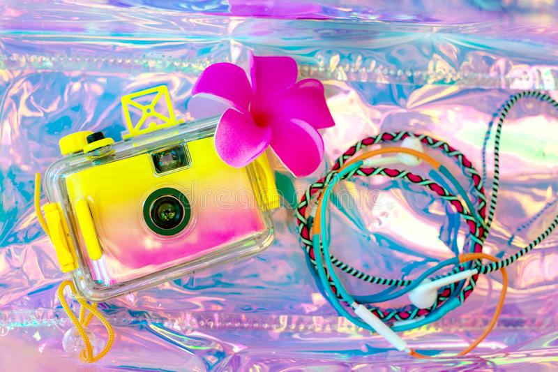 Summer background, beach holiday and travel concept with trendy hologram style bag. Photo camera and colorful headphones stock photography