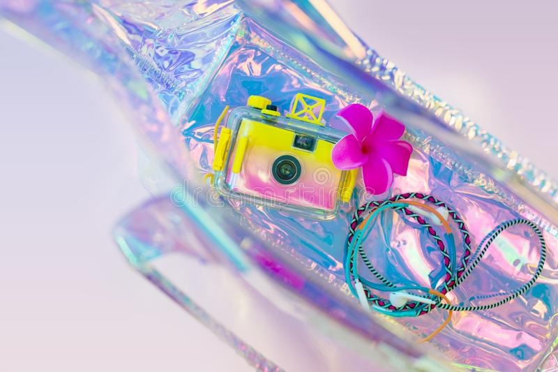 Summer background, beach holiday and travel concept with trendy hologram style bag. Photo camera and colorful headphones stock images