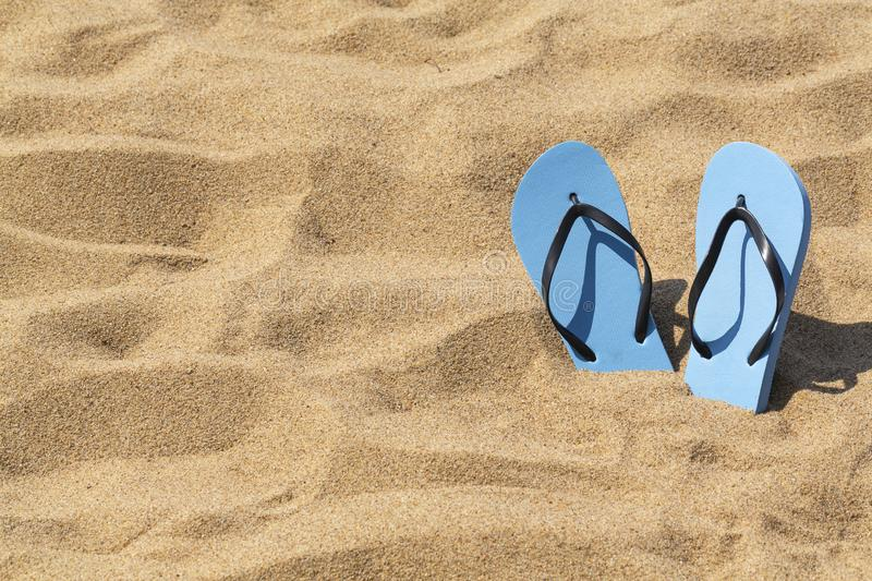 Summer background of beach and shoes on sand. Blue flip flops on the sunny tropical beach. stock photo