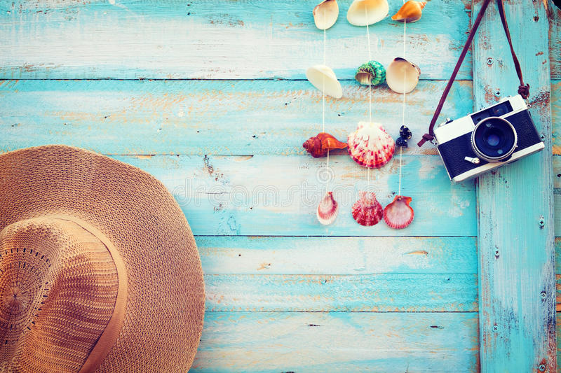 Summer background - The concept of leisure travel in the summer on a tropical beach seaside. Retro camera with straw hat hanging on wood wall background royalty free stock photo