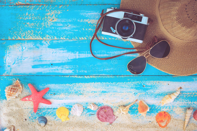 Summer background. The concept of leisure travel in the summer on a tropical beach seaside. retro camera with hat, sunglasses on wood table background royalty free stock photos