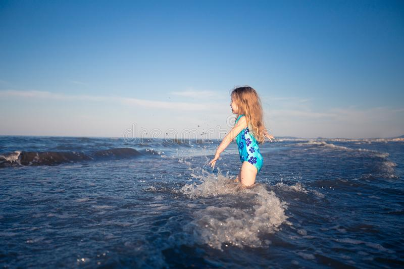 Summer background. Little girl in blue swimsuit standing in blue sea. Happy child royalty free stock photo