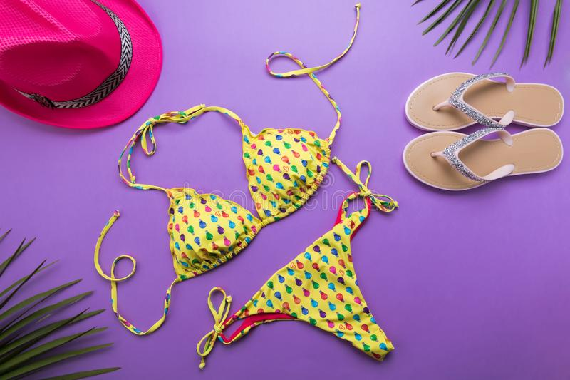 Summer background with palm leaves, pink fashion hat and bikini on violet or purple background, travel and vacations concept, top. Summer background with palm royalty free stock images