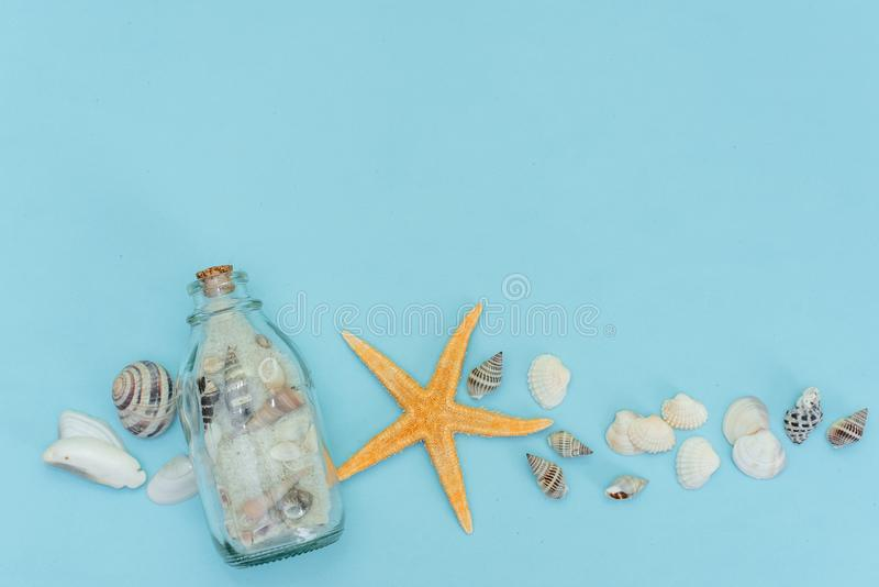 Summer background. Pastel pink woman accessories: straw hat with sunglasses , sea shells and turquoise blue tropical leaves on royalty free stock photo