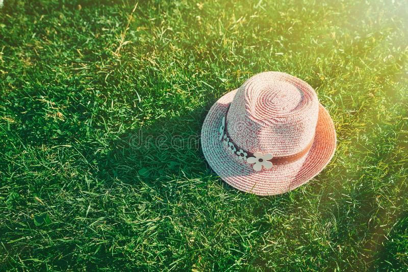 Summer background Pink sunhat on green grass. Pop art design, creative summer party. Minimalism. royalty free stock images
