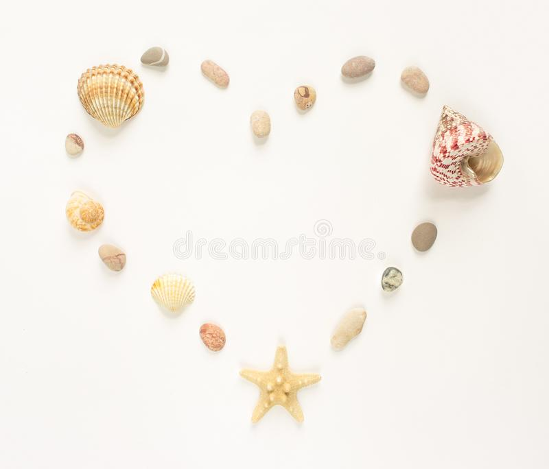 Summer background. Seashells, starfish, sea pebbles on white background. Heart shape. Flat lay, top view. stock images