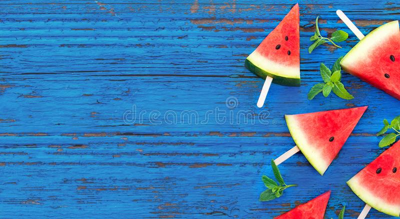 Summer background. Watermelon fruit slice popsicles on a blue w stock photo