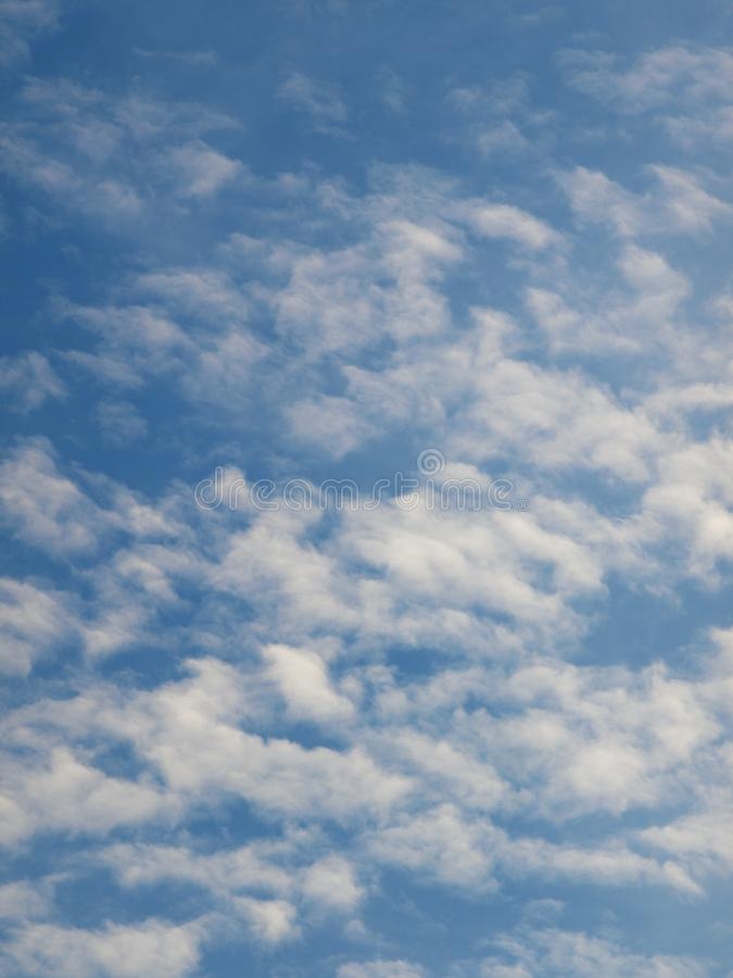Summer background with white flying clouds on blue sky. Romantic natural heaven backdrop. royalty free stock images