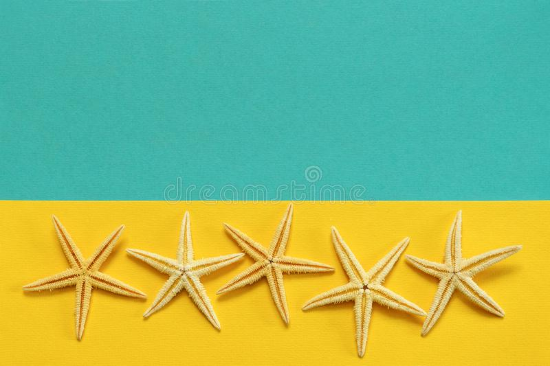 Summer background of yellow and blue paper with starfish, symbol. Izing the sea coast royalty free stock photos