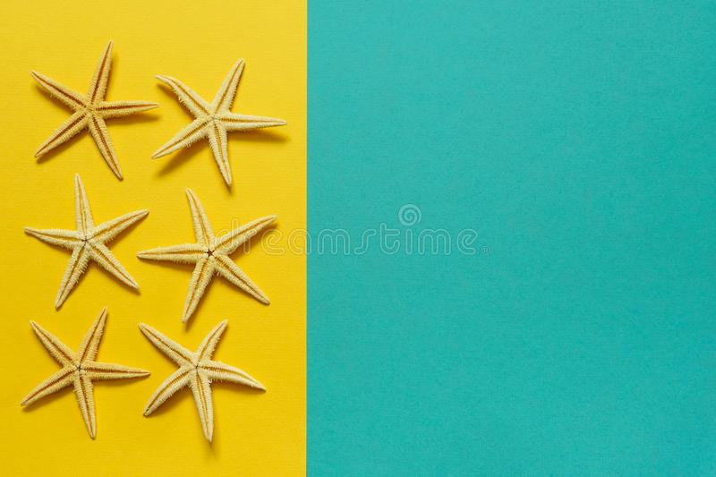 Summer background of yellow and blue paper with starfish, symbol. Izing the sea coast stock image