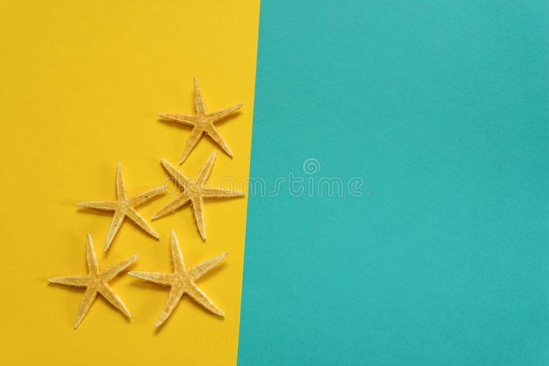 Summer background of yellow and blue paper with starfish, symbol. Izing the sea coast royalty free stock image