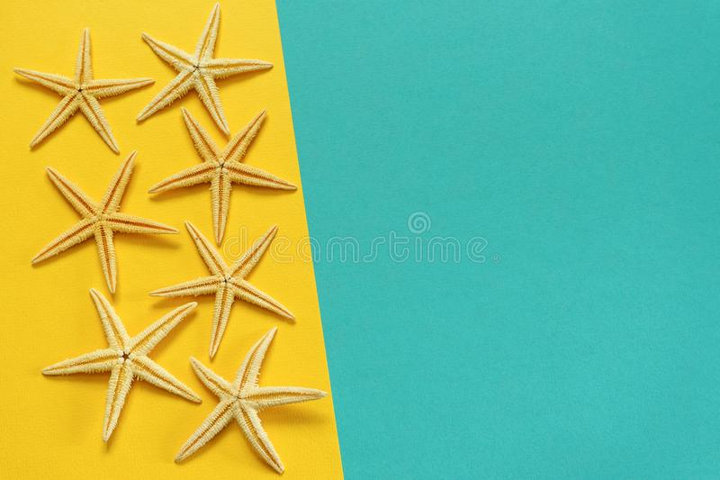 Summer background of yellow and blue paper with starfish, symbol. Izing the sea coast royalty free stock images
