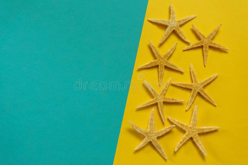 Summer background of yellow and blue paper with starfish, symbol. Izing the sea coast stock images