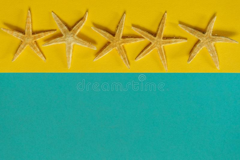 Summer background of yellow and blue paper with starfish, symbol. Izing the sea coast stock photos