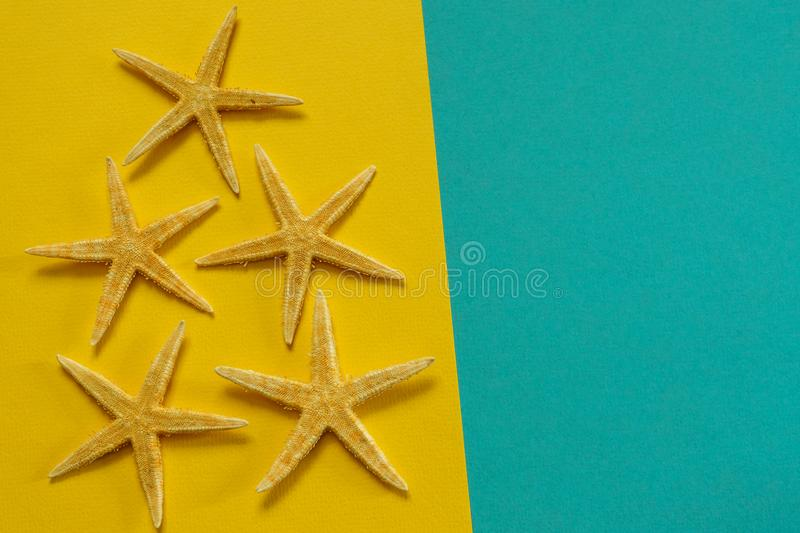 Summer background of yellow and blue paper with starfish, symbol. Izing the sea coast stock photography