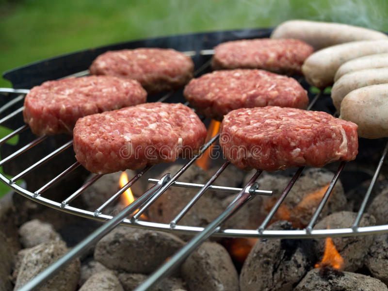 Summer barbecue. A summer barbecue with burgers and sausages royalty free stock photo