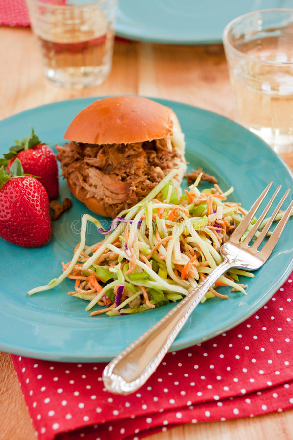 Summer Barbecue. A pulled pork sandwich, fresh strawberries, and Asian dressing broccoli cole slaw sit on a blue plate at a summer barbecue stock photos