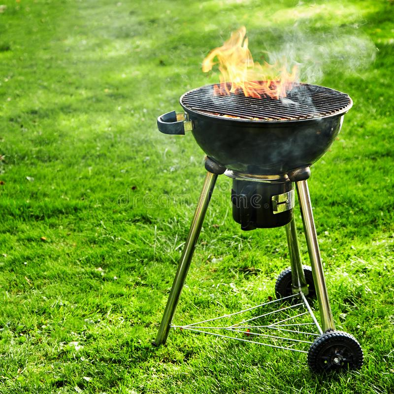 Summer barbecue fire blazing in a kettle grill. Outdoors on green grass with fiery flames as it burns down to hot coals for cooking stock photo