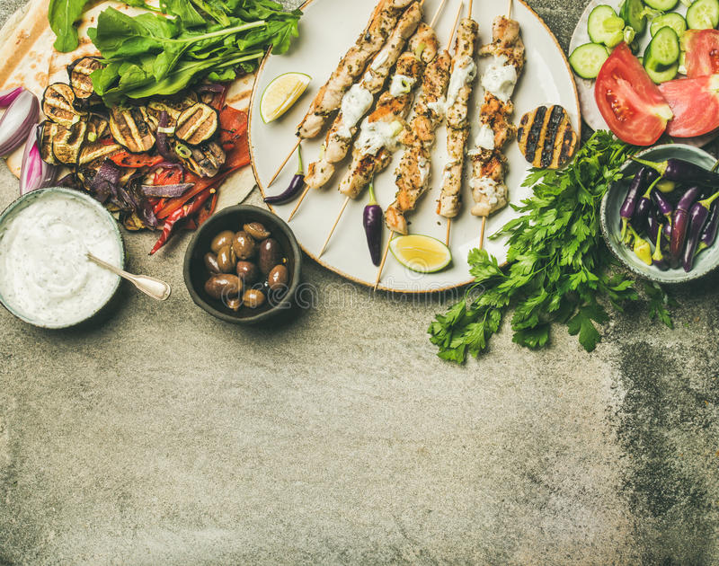 Summer barbecue party dinner set, concrete background, copy space. Summer barbecue party dinner set. Flatlay of grilled chicken skewers with yogurt dip stock image